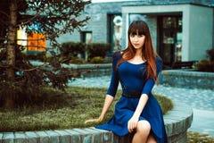 有长的头发的年轻可爱的妇女在与配刀腰带的一身蓝色庄重装束 免版税库存图片