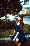 有长的头发的年轻可爱的妇女在与配刀腰带的一身蓝色庄重装束 库存图片