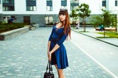 有长的头发的年轻可爱的妇女在与配刀腰带的一身蓝色庄重装束 库存照片