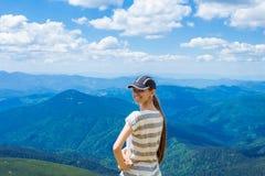 有长的头发的年轻旅游女孩在山顶部的一个盖帽 免版税库存图片