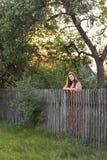 有长的头发的年轻深色的女孩在一件减速火箭的sarafan礼服站立靠近农村篱芭在乡下在日落 库存图片