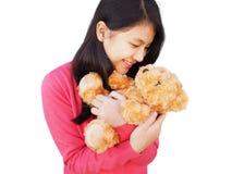 有长的头发的微笑亚裔的女孩变褐在她的胳膊的玩具熊 库存照片