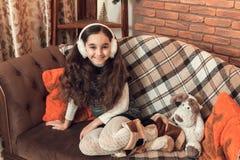 有长的头发的愉快的矮小的深色的女孩坐沙发在c 免版税图库摄影