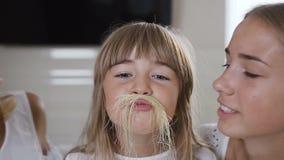 有长的头发的特写镜头迷人的小女孩由玉米头发做一根髭并且看照相机,母亲和老 股票录像