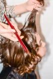 有长的头发的男孩得到他的头发由美发师切开 免版税库存图片