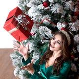 有长的头发的美丽的女孩在有一个王冠的一件绿色礼服在她顶头捉住一个红色礼物盒在装饰的圣诞树附近 库存图片
