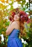 有长的头发的美丽的女孩在蓝色礼服,在红色和绿色花圈远远胜过反对明亮的秋天灌木 免版税库存图片
