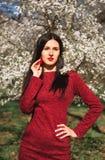 有长的头发的美丽的年轻浅黑肤色的男人在春天的一个公园在一件红色礼服的开花的树中间 免版税库存照片