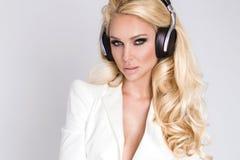 有长的头发的美丽的性感的白肤金发的妇女和坐与耳机的一套典雅的白色衣服的完善的身体 免版税库存照片