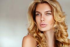有长的头发的美丽,嫩,性感的白肤金发的女孩和没有摆在白色背景的桃红色女用贴身内衣裤的构成的松的嘴唇 免版税图库摄影