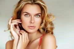 有长的头发的美丽,嫩,性感的白肤金发的女孩和没有摆在白色背景的桃红色女用贴身内衣裤的构成的松的嘴唇 库存照片