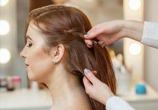 有长的头发的美丽,红发女孩,美发师编织法国辫子, 免版税库存照片