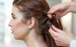 有长的头发的美丽,红发女孩,美发师编织法国辫子, 库存照片