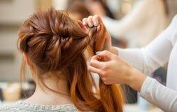 有长的头发的美丽,红发女孩,美发师编织法国辫子 免版税库存照片