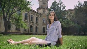 有长的头发的迷人的年轻女性大学生坐草在公园在大学和微笑附近,愉快和 股票录像