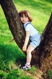 有长的头发的逗人喜爱的小孩儿童男孩在使用与在步行的玩具汽车的时髦的成套装备在夏天或春天庭院里 免版税图库摄影