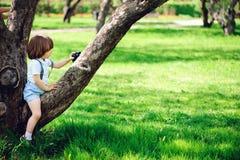 有长的头发的逗人喜爱的小孩儿童男孩在使用与在步行的玩具汽车的时髦的成套装备在夏天 库存照片