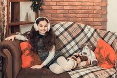 有长的头发的逗人喜爱的矮小的深色的女孩坐沙发在ch 库存照片