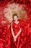 有长的头发的金发碧眼的女人在红色织品 库存照片