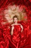 有长的头发的金发碧眼的女人在红色织品 图库摄影