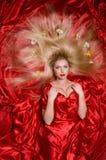 有长的头发的金发碧眼的女人在红色织品 库存图片