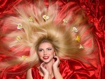 有长的头发的金发碧眼的女人在红色织品 免版税库存图片