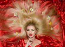 有长的头发的金发碧眼的女人在红色织品 免版税库存照片