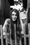 有长的头发的,画象年轻女性,站立在木篱芭附近在村庄 免版税库存照片