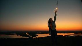有长的头发飞行的愉快的少妇在举有闪烁发光物的风手在小山的夏天日落 股票录像