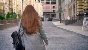 有长的姜头发的回顾的少妇走在城市和,拿着背包,都市街道背景,后面 影视素材