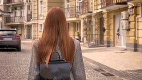 有长的姜头发的回顾的少妇走在城市街道上和,拿着背包,都市街道背景 股票录像