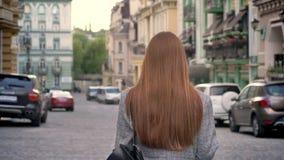 有长的姜头发的少妇走在城市和拿着在一肩膀,都市街道背景的背包 影视素材