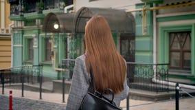 有长的姜头发的少妇走在街道和拿着在一肩膀,绿色大厦背景的背包 影视素材