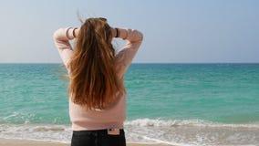 有长的姜头发身分在海滩和享用的梦想的女孩使海景,使用与她的头发的海风惊奇 库存图片