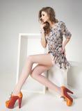 有长的性感的腿的美丽的妇女在夏天礼服摆在 库存图片