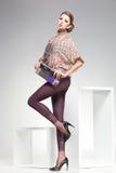 有长的性感的腿的美丽的妇女在演播室穿戴了典雅摆在 免版税图库摄影