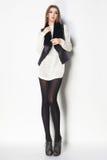 有长的性感的腿的美丽的妇女穿戴了典雅摆在Th 免版税库存照片