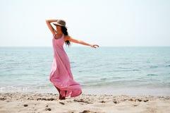 有长的桃红色礼服和太阳帽子的美丽的妇女在热带b 免版税库存照片