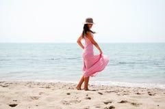 有长的桃红色礼服和太阳帽子的美丽的妇女在热带b 免版税库存图片