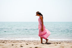有长的桃红色礼服和太阳帽子的美丽的妇女在热带b 免版税图库摄影