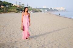 有长的桃红色礼服的美丽的妇女在一个热带海滩 库存图片