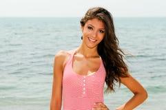 有长的桃红色礼服的美丽的妇女在一个热带海滩 图库摄影