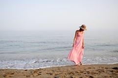 有长的桃红色礼服的美丽的妇女在一个热带海滩 免版税库存图片
