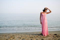 有长的桃红色礼服的美丽的妇女在一个热带海滩 免版税图库摄影