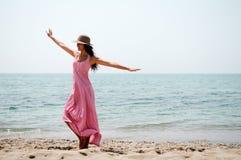 有长的桃红色礼服的美丽的妇女在海滩 图库摄影