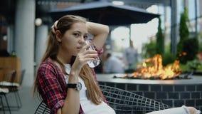 有长的棕色坐在城市街道咖啡馆和饮料冷水的头发和便衣的可爱的女孩 股票视频