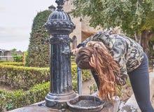 有长的棕色头发的一个年轻少年,在卡斯蒂略克萨蒂瓦里面的一个喷泉喝着在巴伦西亚,西班牙 免版税库存照片