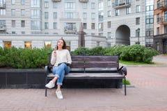 有长的棕色头发的一个美丽的女孩坐与书和尖酸的玻璃的长凳,当读时 她离开了房子  免版税库存照片