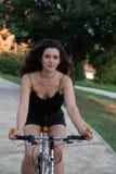 有长的棕色头发的女孩,循环在一条狭窄的街道上在城市公园 库存图片