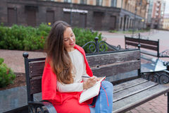 有长的棕色头发和白色牙微笑的一个可爱的女孩在都市背景坐长凳并且写她想法  库存图片